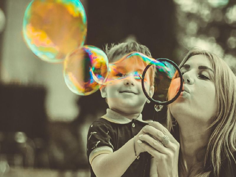 Mum and son blow bubbles.