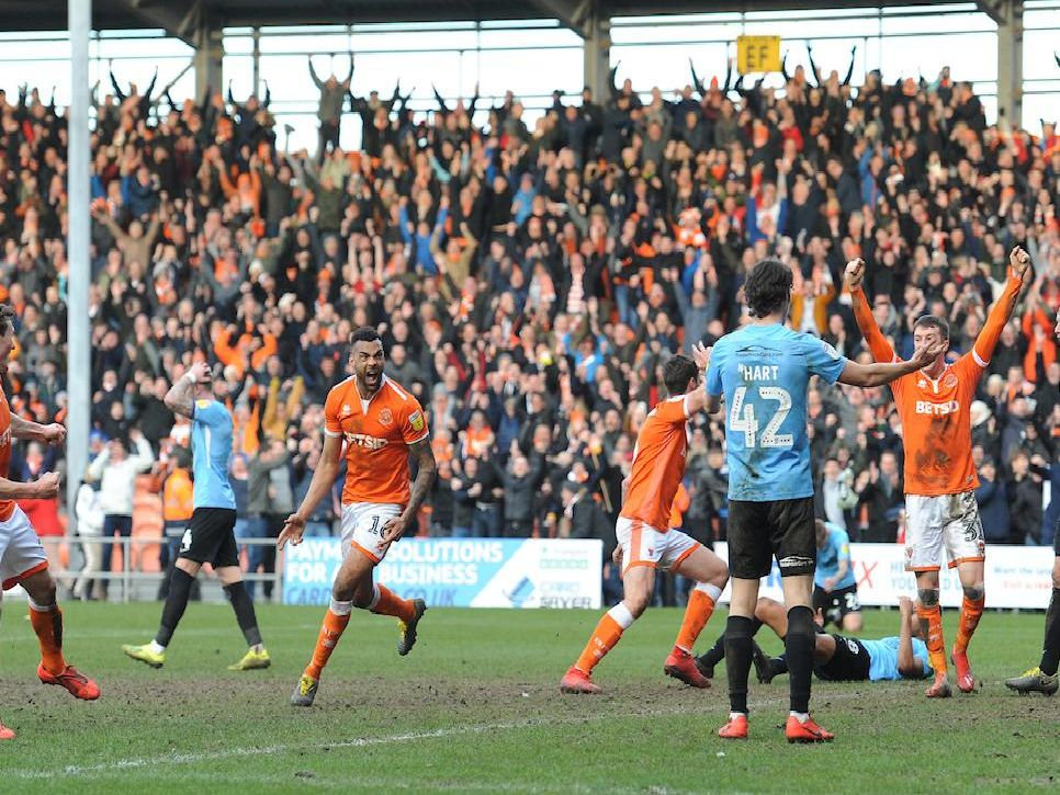 Blackpool's players and supporters celebrate their 96th-minute equaliser