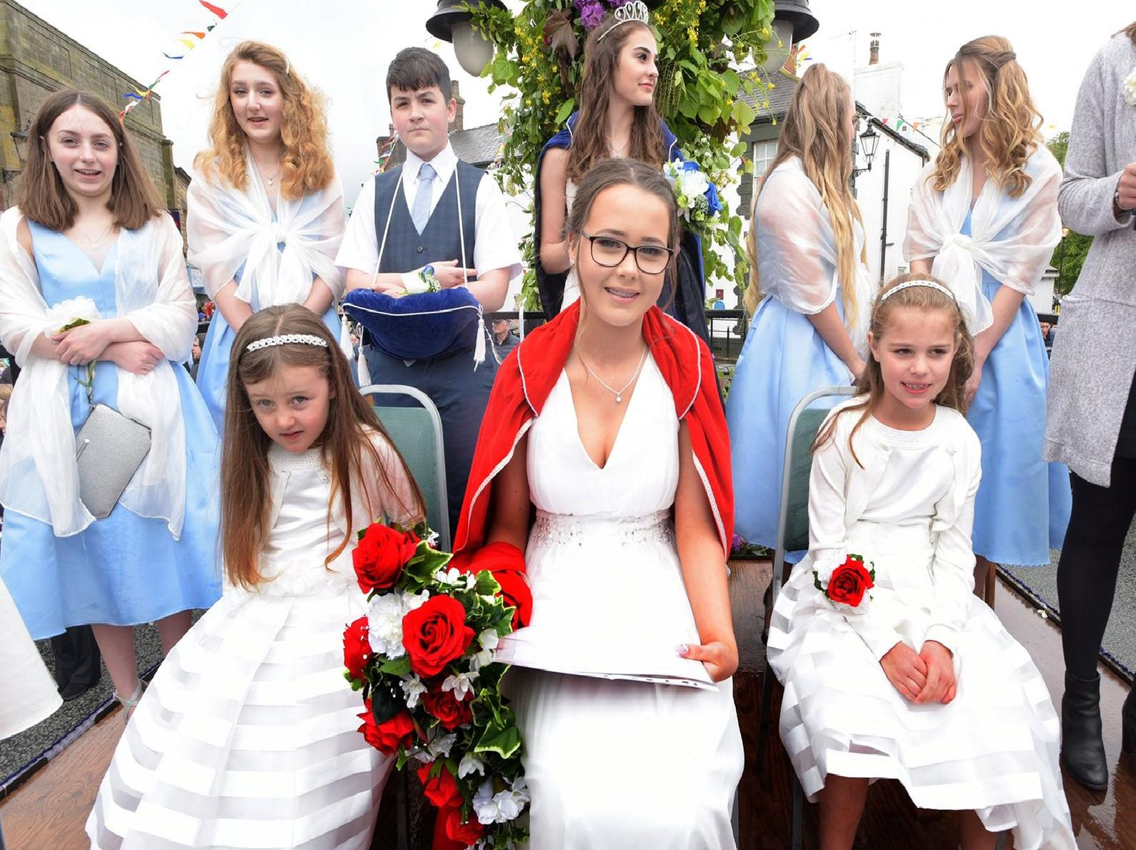 Retiring Queen Ellen QWellings and 2019 Queen Emily Guy and entourage in Garstang's Annual Children's Festival parade.