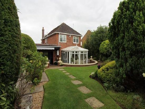 To the rear, the home has manicured gardens .