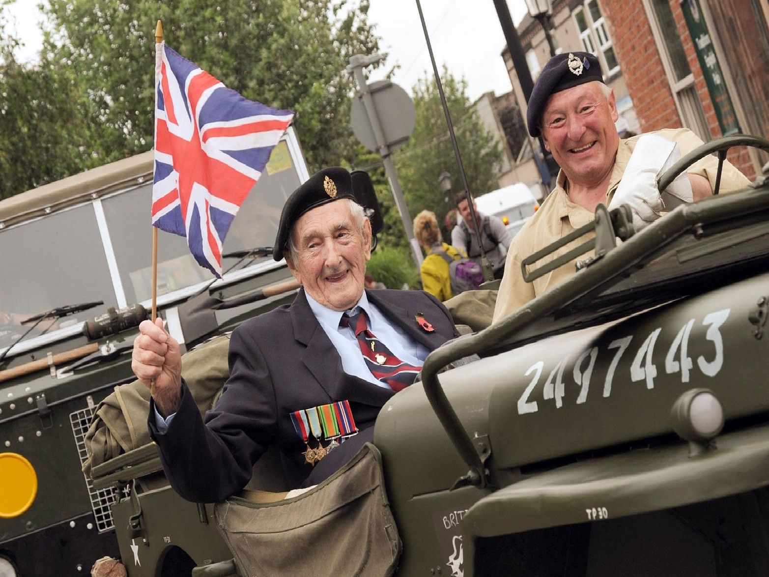 Royal Air Force veteran John Wilson flies the flag with driver Tony Bryan in a 1944 Willis Jeep at the procession's vanguard.