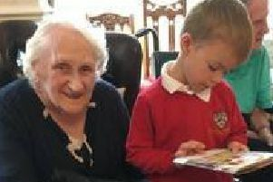 A pupil from Goosnargh Oliverson's CE Primary School reads to a resident of Bushell House.