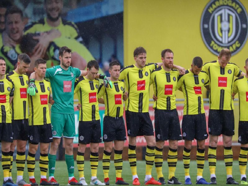 Harrogate Town line-up for Saturday's minute's silence in memory of former chairman Bill Fotherby. Pictures: Matt Kirkham