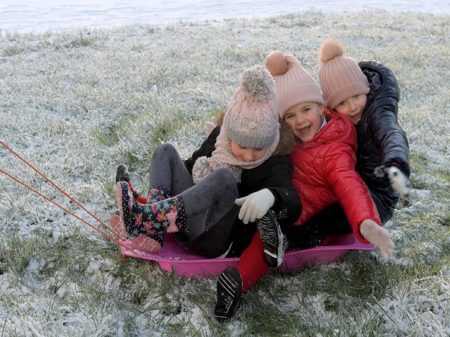 Freya Burns, Skye and Tilly Sutcliffe on the sled. Photo: Neil Cross