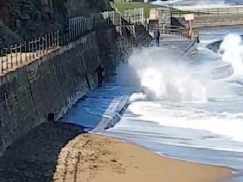 Three people, with two dogs, walk beside the sea wall along from Scarborough Spa, as waves crash in.