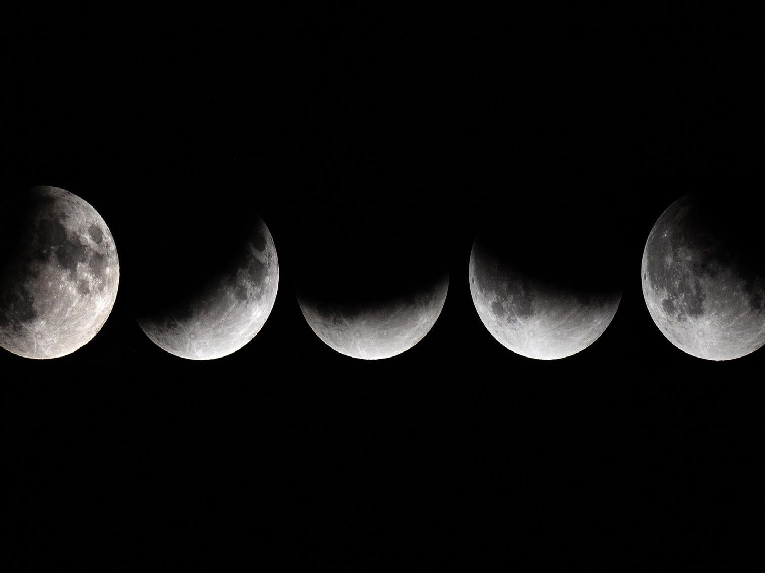 This combination of pictures shows the moon in various stages of a partial lunar eclipse as seen from Vienna