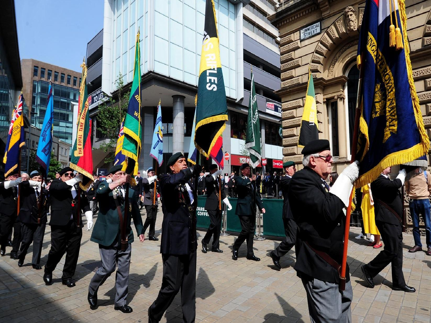 Flag bearers march down Commercial Street in Leeds city centre.