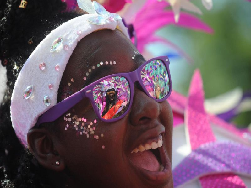 Leeds Carnival Queen Tahiela Odain Hamilton is reflected in the glasses of Eleanor Claxton