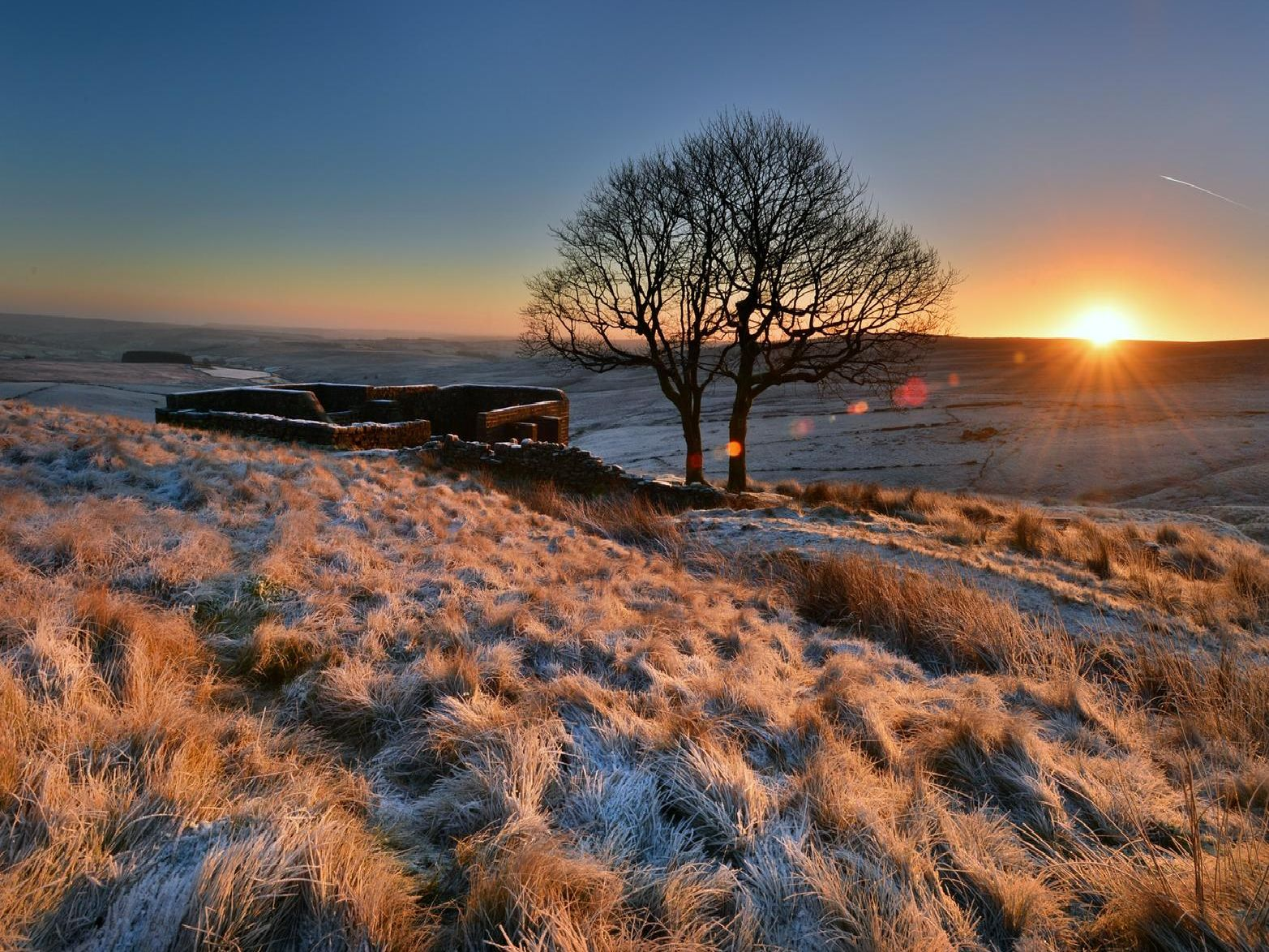 The Sun rises above a frosty Top Withens high in the Pennines above Haworth, the inspiration Wuthering Heights.