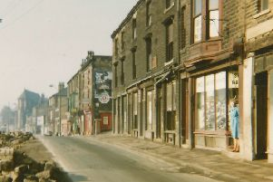 Huddersfield Road where all the properties were demolished to make way for a dual carriageway. The lady in blue is standing in the doorway of Archer's shoe shop ' the last to be demolished.