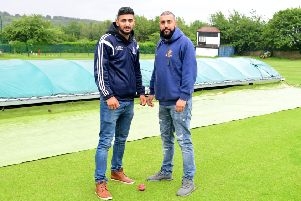 Batley captain Roheil Hussain batley and East Bierley's Raheel Ahmed inspect the covers last Saturday when the entire Bradford League programme washed out. Picture: Paul Butterfield