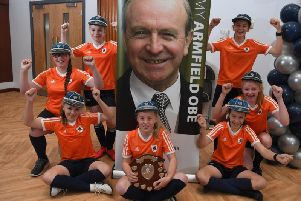 The successful Year Seven girls football team (now in Year Eight) with their trophy, wearing some of Jimmy Armfield's Englad caps at Armfield Academy
