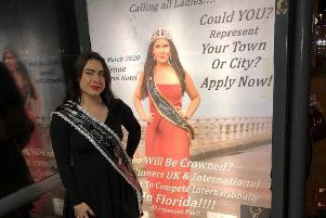 Bethan Mcauley, a contestant in this year's competition Miss Elegance of the World, standing next to a poster at a Blackpool bus stop