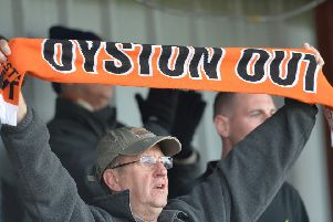 A Blackpool fan holds up his protest scarf at Fleetwood last week