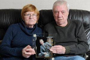 Rose and Martin Loder hold up a picture of their beloved son