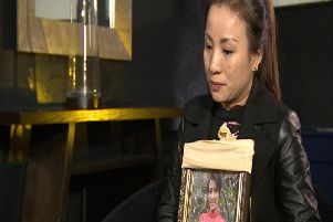 Quynh, holding a framed photo of Quyen