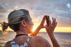 Female photographer taking pictures on peer sunset, lowlight, solar flare, sun flare, head and shoulders, wind blowing hair, dramatic scene