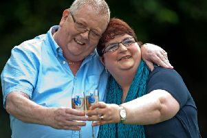 Colin Weir (L) and his wife Chris pose for pictures with champagne during a photocall in Falkirk, Scotland, on July 15, 2011 (Wattie Cheung/AFP/Getty Images)