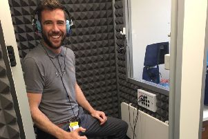Senior Audiologist Alex Trousdale demonstrates the new soundproof booth