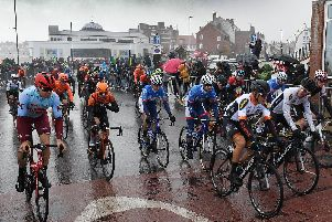 Rain lashes the riders on the start line, as stage three gets underway.