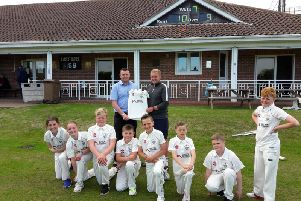 Mark Purvis of Burton Roofing Merchants Ltd presenting team manager Elliot Traves and the Bridlington CC Under-11s team with the new sponsored shirts.