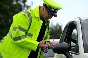 A policeman with a breathalyser.