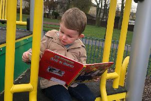 Myles Caldecott (two) is engrossed in the book he chose from the Ightenhill little free library.