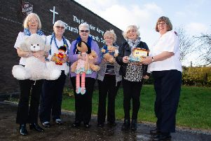 Captain Maisie Veacock (right) hands over gifts to Burnley Express reporter Sue Plunkett watched by Salvation Army volunteers.