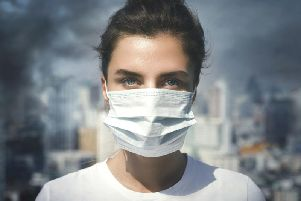 A woman wearing a face mask as protection from pollution. Picture credit: iStock/PA