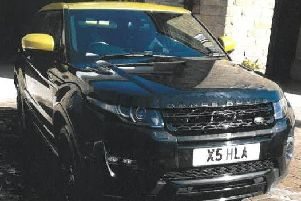 A stolen black Range Rover Evoque which has a yellow roof.