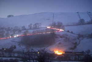 Cars making their way up and down a hill near Crowdecote in the Peak District after snowfall on Friday evening. Photo: Rod Kirkpatrick / F Stop Press.