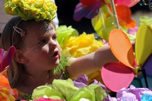 A youngster peaks through a floral float.