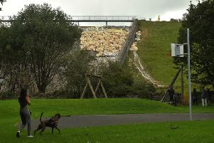 A woman walks her dog below the damaged section of the Toddbrook Reservoir dam, which is filled with bags of aggregate to reinforce the structure. Photo: OLI SCARFF/AFP/Getty Images.