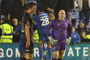 A disappointed Mansfield goalkeeper Conrad Logan as Shrewsbury's Brad Walker celebrates their second goal in injury time last weekend.
