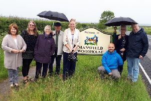 Councillors and members of the Mansfield Woodhouse Community Development Group pictured with the new 'Welcome to Mansfield Woodhouse' sign, on Peafield Lane.