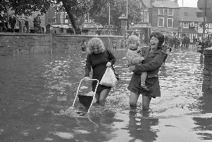 These ladies are still having a giggle while trying to get their shopping and pushchair through the water.
