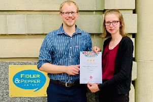 Emma Grieves, of Fidler & Pepper, receives the certificate from Tom Wyke, of Christian Aid.