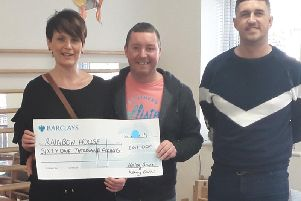 Helen Barron and Kenny Burns, of Lostock Hall, present a cheque to families who receive support at Rainbow House, in Mawdesley