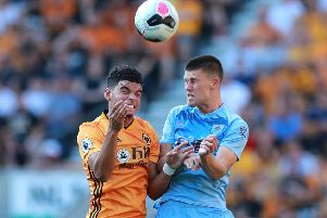 WOLVERHAMPTON, ENGLAND - AUGUST 25: Johann Berg Gudmundsson of Burnley and Morgan Gibbs-White of Wolverhampton Wanderers clash for a header during the Premier League match between Wolverhampton Wanderers and Burnley FC at Molineux on August 25, 2019 in Wolverhampton, United Kingdom. (Photo by David Rogers/Getty Images)