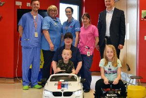 Four-year-old Tobiasz Wusiewicz from Burnley became the first child to test drive the Bowker BMW baby racer, watched by (from left) Dr Ian Clegg, Staff Nurses Gillian Brand and Charlotte Caffrey, Play Leader Angela Ashton, Bowker BMW Managing Director Chris Eccles and (front) Sister Rita Ogden