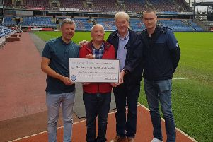 Barry Kilby receives a cheque from Anthony and Tony Carter and Ryan Strange