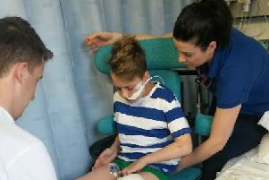 Joe Boyer, 14, pictured in hospital after being hit by a motorbike.