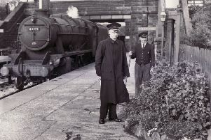 Bamford Railway Station were the winners of the special class prize and shield in the Station Gardens Competition and here Stationmaster, F. Bamford, and a porter admire some of the blooms as a goods train passes through - 4th October 1956