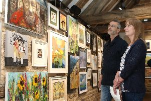 Volunteer stewards Gary Ruddle and Leigh Smith admire the works in the open art exhibition