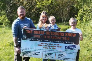 Mark and Becky Roberts with two of their children holding a banner advertising the show.