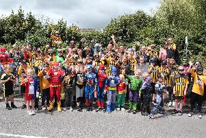 Heroes and villains line up for a photo call before setting off on the procession to the carnival ground.