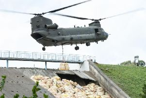 A Chinook helicopter drops sandbags onto the dam wall at Toddbrook Reservoir. Photo: Leon Neal/Getty Images.