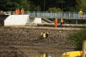 Engineers and members of the emergency services work to pump water from Toddbrook Reservoir. Photo: Oli Scarff/AFP/Getty Images.