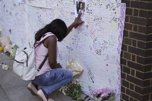 A woman touches a missing poster for 12-year-old Jessica Urbano on a tribute wall after laying flowers on the side of Latymer Community Church next to the fire-gutted Grenfell Tower in London.