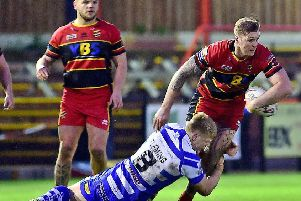 Dewsbury's Lucas Walshaw is tackled by Halifax defender Dan Fleming during Friday's Challenge Cup tie.